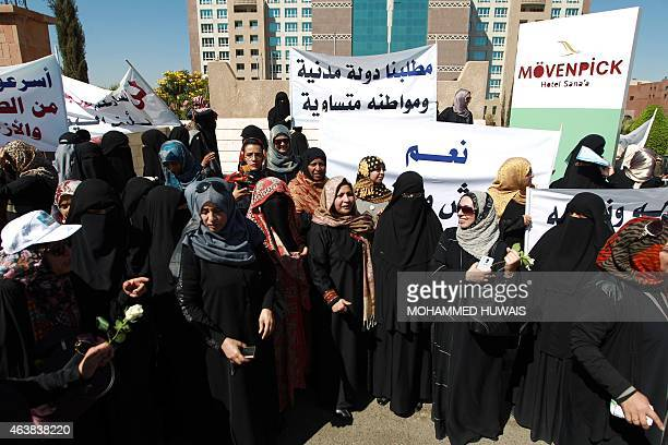 Members of Yemeni women's unions hold banners during a rally calling for more gender equality in decision making and for an end to the country's...