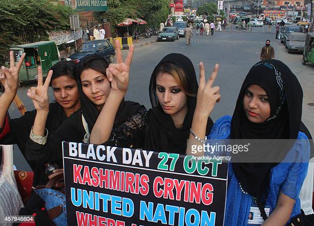 Members of Youth Forum for Kashmir hold placards and and flash V sign during the protest against Indian presence in the Himalayan region in Lahore...