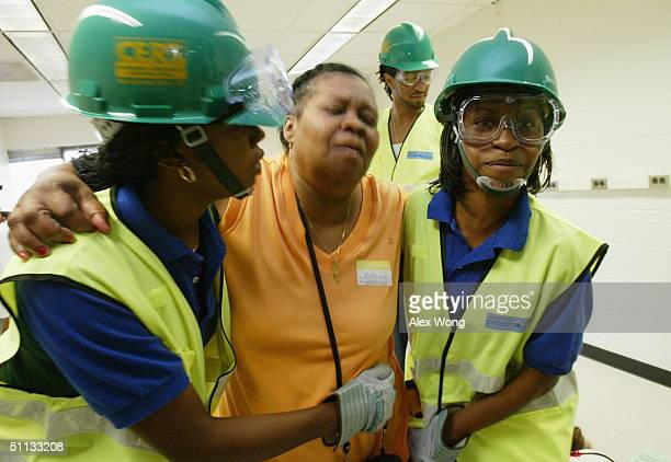 Members Sharece Crawford and Jasmin Drain of Team DC escort an unidentified victim during a drill test of a simulated disaster situation as part of...