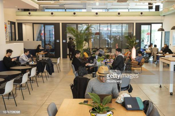 Members sit and use laptop computers at the WeWork Cos. Iceberg co-working space in Tokyo, Japan, on Thursday, Dec. 20, 2018. The office-sharing...