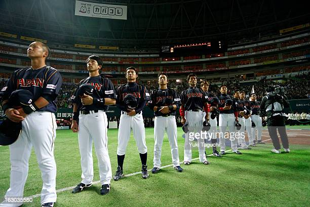Members Team Japan are seen on the base path during the national anthems before the Pool A Game 1 between Team Japan and Team Brazil during the first...