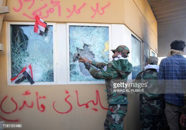TOPSHOT Members the Hashed alShaabi a mostly Shiite network of local armed groups trained and armed by powerful neighbour Iran smash the bulletproof...