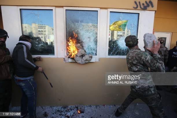 Members the Hashed alShaabi a mostly Shiite network of local armed groups trained and armed by powerful neighbour Iran smash the bulletproof glass of...