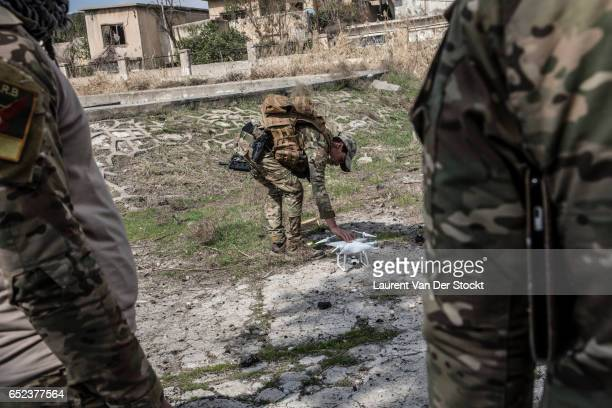 Members the the Iraqi government's Emergency Response Division are operating reconnaissance operation by drone in a district taken back from the...