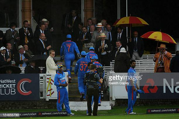 MCC members use umbrellas to shelter from the rain as India players make their way into the pavilion after rain interrupted play on 4th Natwest One...