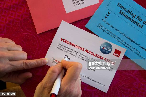 SPD members vote to form a grand coalition between the SPD and the CDU The picture shows the election ducuments with the ballot paper A hand makes...