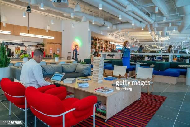 Members work in a cafeteria and lounge area at the WeWork Cos Inc. 85 Broad Street offices in the Manhattan borough of New York, U.S., on Wednesday,...