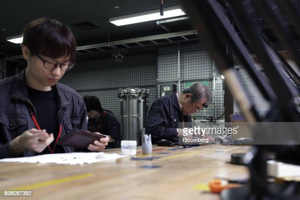 Members work in a workshop at the DMMmake Akiba hardware incubation space operated by DMMcom Ltd in Tokyo Japan on Tuesday July 18 2017 After years...