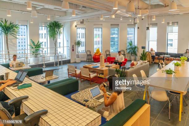 Members work in the cafeteria at the WeWork Cos Inc. 85 Broad Street offices in the Manhattan borough of New York, U.S., on Wednesday, May 22, 2019....