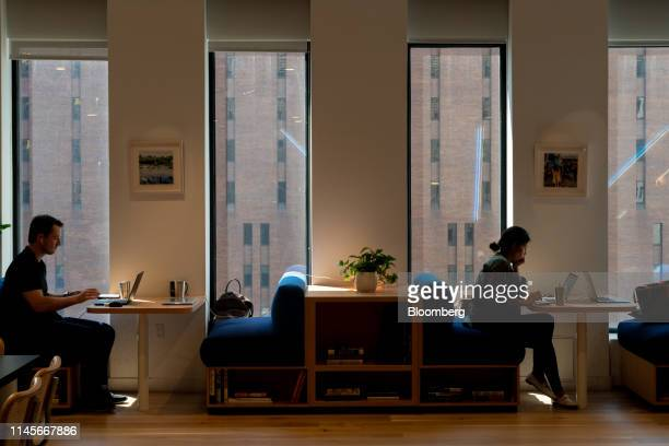 Members work on laptop computers in a common area at the WeWork Cos Inc. 85 Broad Street offices in the Manhattan borough of New York, U.S., on...