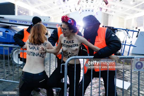 Membersof feminist movement Femen are evacuated by members of the security after demonstrating near the Arc de Triomphe on November 10 as several...