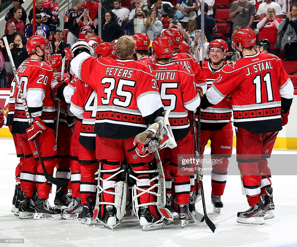 Membes of the Carolina Hurricanes gather on the ice to celebrate their victory over the New York Islanders during their NHL game at PNC Arena on April 23, 2013 in Raleigh, North Carolina.