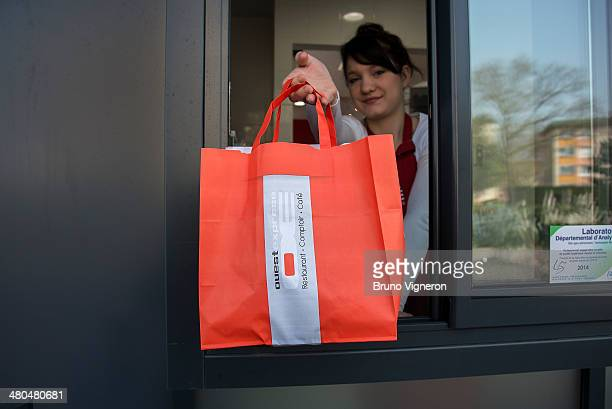 A memeber of staff passes a food order to a customer in a car at the drivethru of Paul Bocuse's 'Ouest Express' fast food restaurant on March 13 2014...