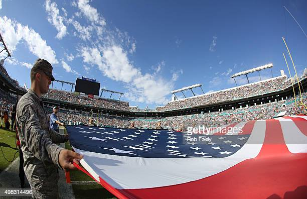 Memebers of the US Armed Forces hold an American Flag on the field for the singing of God Bless America during the second quarter of the game between...