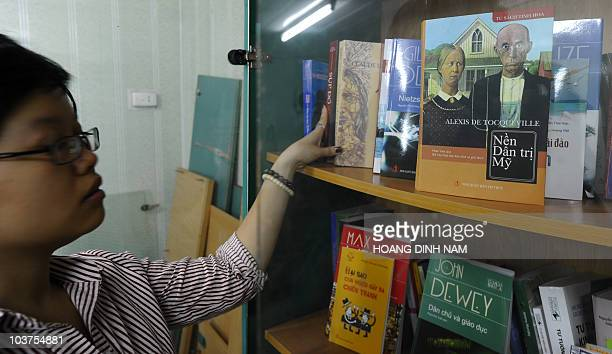 A memebr of staff of the publishing house Tri Thuc shows off the book 'Democracy in American' by Alexis de Tocqueville in Hanoi on August 31 2010 The...