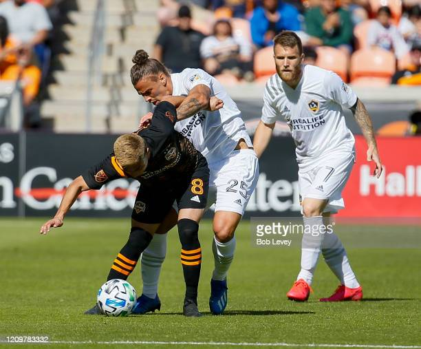 Memo Rodriguez of Houston Dynamo holds off from Rolf Feltscher of Los Angeles Galaxy and Aleksander Katai at BBVA Stadium on February 29 2020 in...