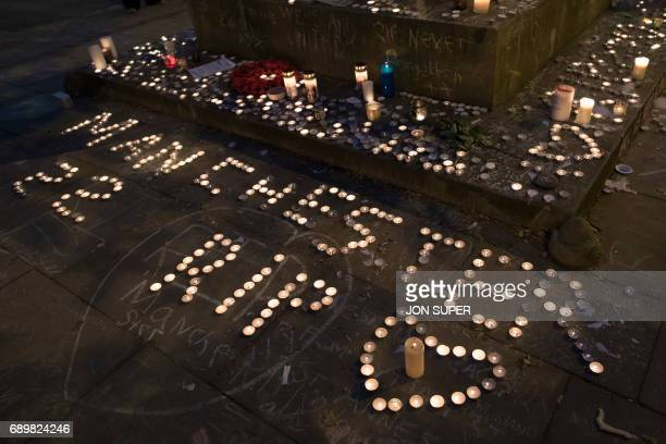 Memorial candles are seen during a vigil on St Ann's Square in Manchester northwest England on May 29 exactly one week after a bomb attack at...