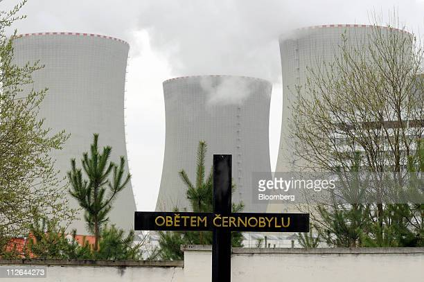 A memorial cross commemorating victims of the Chernobyl nuclear disaster stands in the local cemetery beside the cooling towers of Temelin nuclear...