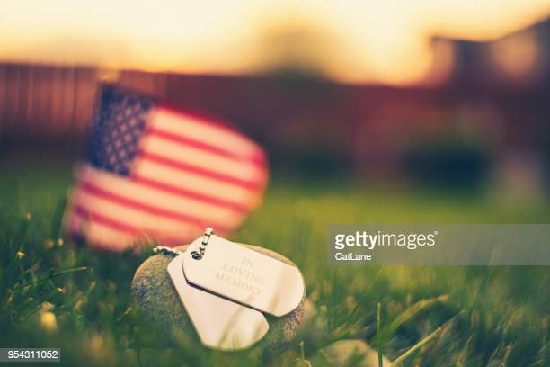 memorial day flag and dog tags in evening sunshine - military flags stock photos and pictures