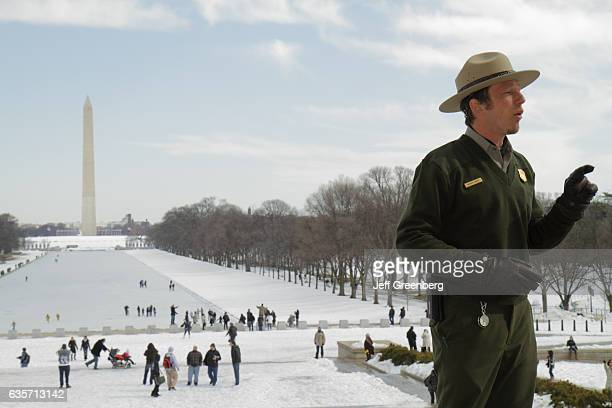 Memorial guide talking in front of the National Mall and Memorial Parks Reflecting Pool which is frozen