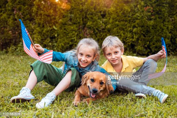 usa memorial or independence day concept with girl and boy holding american flags - memorial day dog stock pictures, royalty-free photos & images