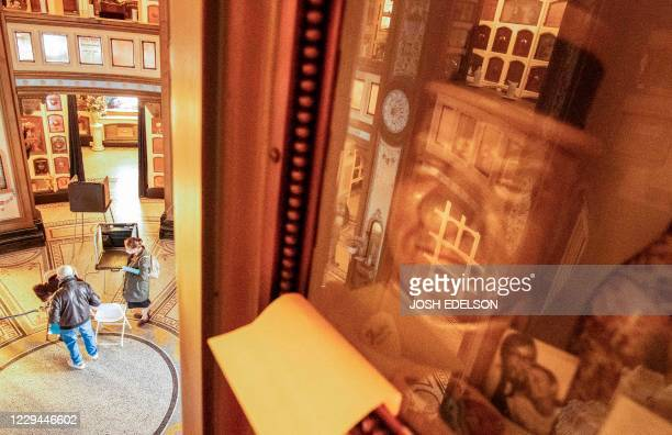 A memorial reflects from behind glass as voters fill out their ballots in a polling station at the San Francisco Columbarium Funeral Home in San...