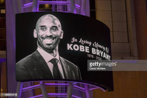 Memorial signage hangs near people mourning for former NBA star Kobe Bryant who was killed in a helicopter crash in Calabasas California near Staples...