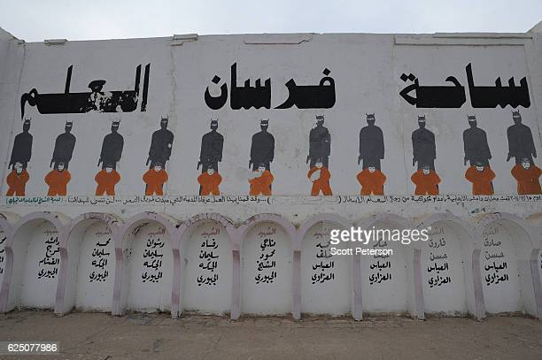 A memorial stands to 11 men wearing orange jumpsuits executed by masked members of the Islamic State in December 2014 for defying ISIS rule at the Al...