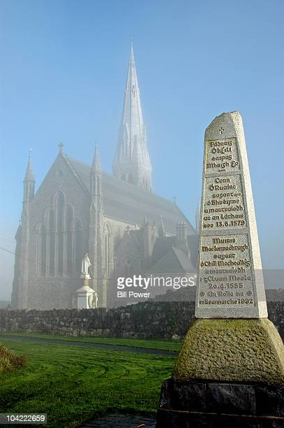 Memorial to the Kilmallock Martyrs, with the Saints Peter and Paul parish church in the background. Taken on a foggy December morning in 2004 as the...