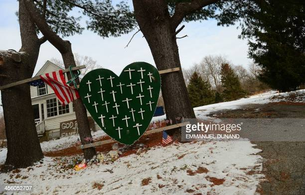 A memorial to victims of last year's Sandy Hook elementary school victims is seen in front of a house in Newtown Connecticut on December 13 2013...