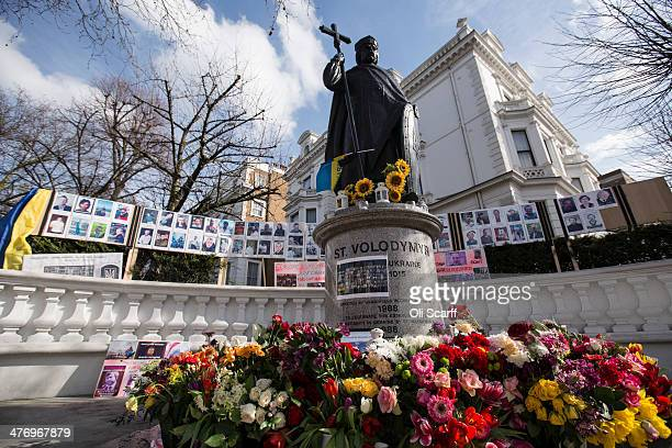 Memorials and floral tributes dedicated to protesters who were killed in recent clashes with security forces in Kiev surround a statue of 'Vladimir...