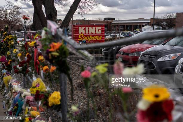 Memorials and flowers are left on the fencing surrounding the grocery store the day after a gunman opened fired at a King Sooper's grocery store on...