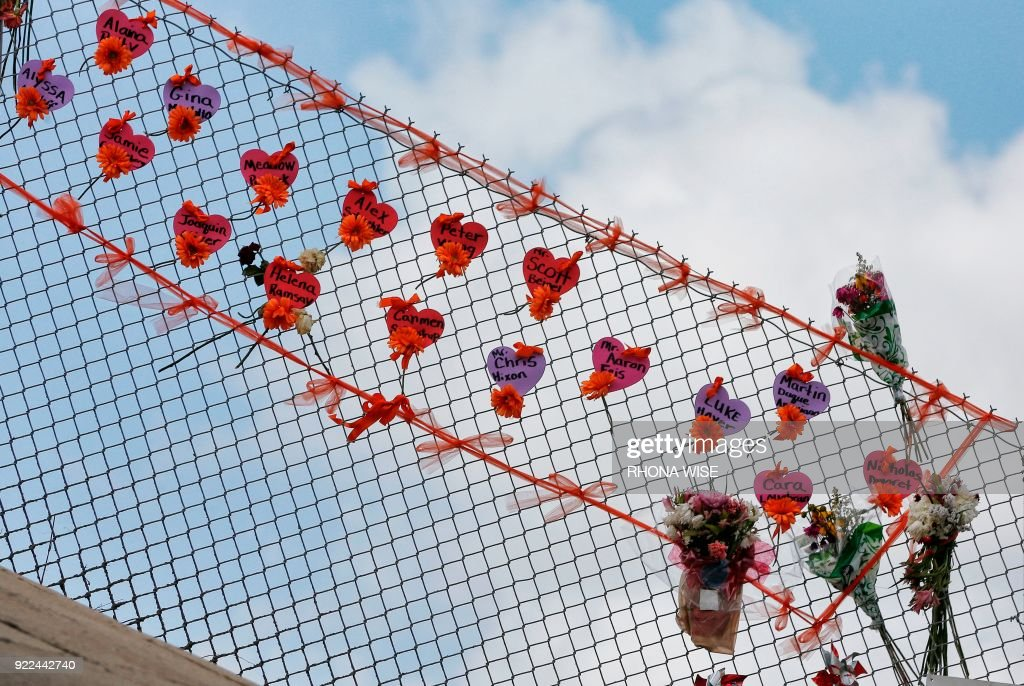 TOPSHOT - Memorials are seen on a fence surrounding Marjory Stoneman Douglas High School in Parkland, Florida on February 21, 2018. A former student, Nikolas Cruz, opened fire at Marjory Stoneman Douglas High School leaving 17 people dead and 15 injured on February 14. /