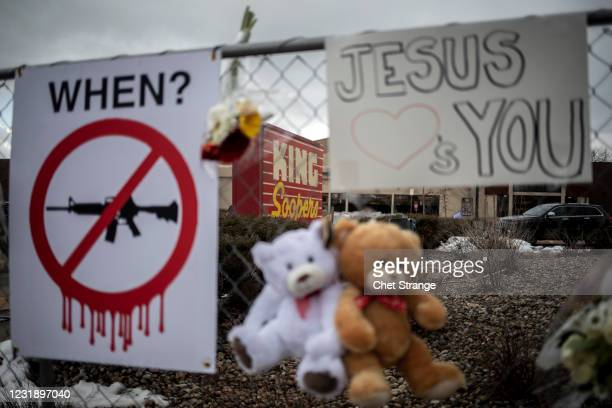 Memorials with signs, teddy bears and flowers are left on the fencing surrounding the grocery store the day after a gunman opened fired at a King...