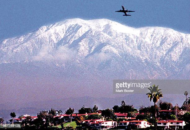 MEMountainViewSnow022796MB–––A plane takes off from John Wayne Airport with snow covered Mount Baldy in the background as viewed from Newport Dunes...