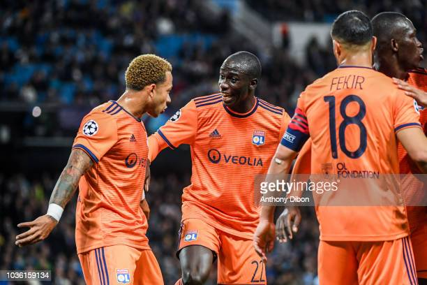 Memphis Depay and Ferland Mendy of Lyon celebrate a goal during the Champions League match between Manchester City and Lyon at Etihad Stadium on...