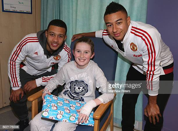 Memphis Depay and Jesse Lingard of Manchester United meet Daniel from Preston as part of the club's annual Christmas hospital visits at Royal...