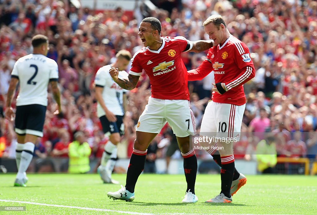 Memphis Depay (C) and Wayne Rooney (R) of Manchester United celebrate their first goal scored by Kyle Walker (L) of Tottenham Hotspur during the Barclays Premier League match between Manchester United and Tottenham Hotspur at Old Trafford on August 8, 2015 in Manchester, England.