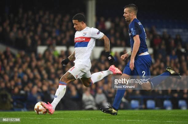 Memphis Depay of Lyon beats Morgan Schneiderlin of Everton to shoot at goal during the UEFA Europa League Group E match between Everton FC and...