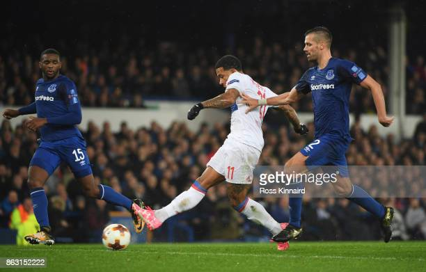 Memphis Depay of Lyon holds off Morgan Schneiderlin of Everton to shoot at goal during the UEFA Europa League Group E match between Everton FC and...