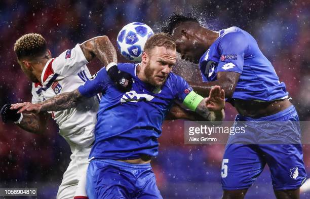 Memphis Depay of Lyon jumps for a header with Kevin Vogt and Kasim Adams Nuhu of Hoffenheim during the Group F match of the UEFA Champions League...