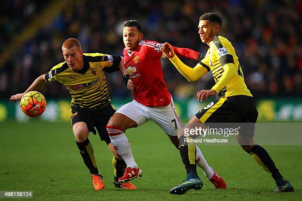 Memphis Depay of Manchester United competes for the ball against Ben Watson and Etienne Capoue of Watford during the Barclays Premier League match...
