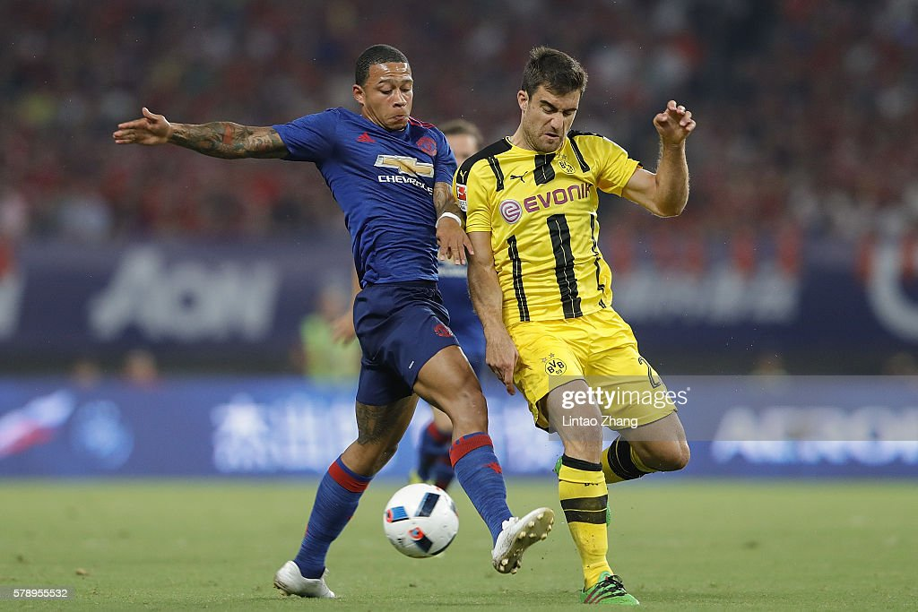 Memphis Depay (L) of Manchester United competes for the ball with Marcel Schmelzer of Borussia Dortmund during the International Champions Cup match between Manchester United and Borussia Dortmund at Shanghai Stadium on July 22, 2016 in Shanghai, China.