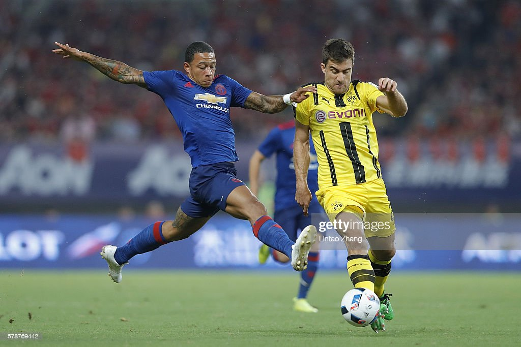 Memphis Depay (L) of Manchester United competes for the ball with Sokratis Papastathopoulos of Borussia Dortmund during the International Champions Cup match between Manchester United and Borussia Dortmund at Shanghai Stadium on July 22, 2016 in Shanghai, China.