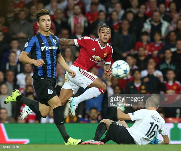 Memphis Depay of Manchester United in action with Dion Cools and Sebastien Bruzzese of Club Brugge during the UEFA Champions League playoff first leg...