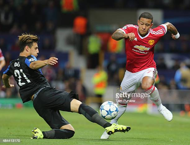 Memphis Depay of Manchester United in action with Dion Cools of Club Brugge during the UEFA Champions League playoff first leg match between...