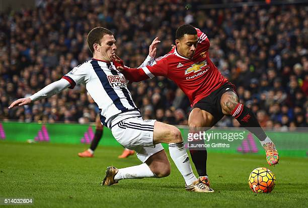Memphis Depay of Manchester United is tackled by Craig Gardner of West Bromwich Albion during the Barclays Premier League match between West Bromwich...