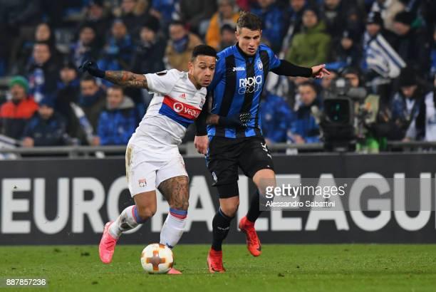 Memphis Depay of Olympique Lyon competes for the ball whit Rafael Toloi of Atalanta during the UEFA Europa League group E match between Atalanta and...