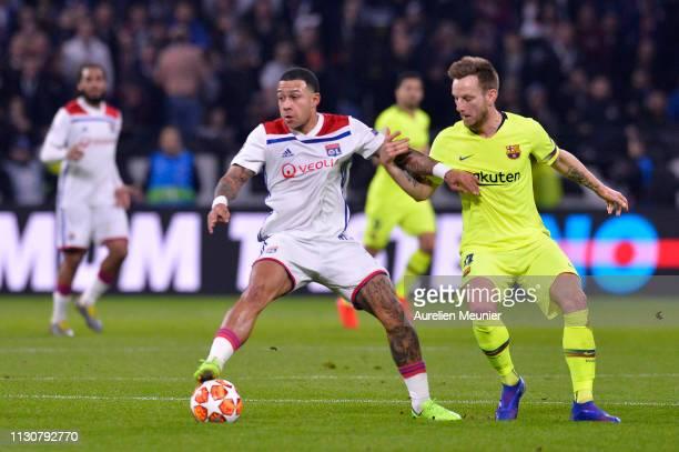 Memphis Depay of Olympique Lyonnais and Ivan Rakitic Of FC Barcelona fight for the ball during the UEFA Champions League Round of 16 First Leg match...