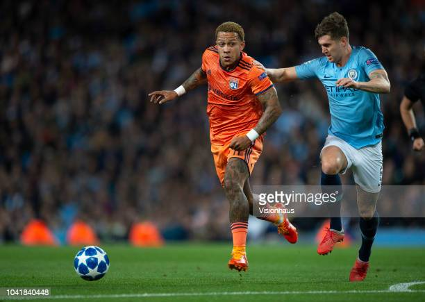 Memphis Depay of Olympique Lyonnais and John Stones of Manchester City in action during the Group F match of the UEFA Champions League between...
